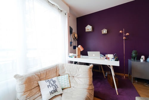 Contemporary Home Office With Purple Walls, A Freestanding Desk And A  Cushioned Seating.