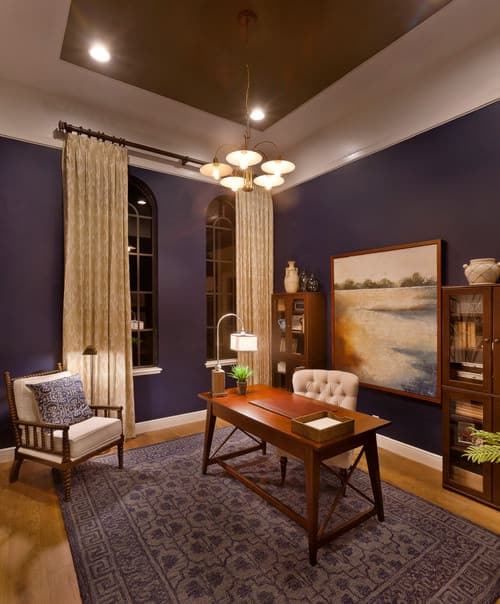 Farmhouse home office with purple walls featuring a large painting between two bookcases.