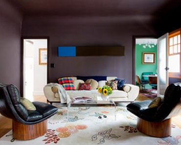 Contemporary purple living room with a sofa, double back chairs, lucite table, hardwood flooring and a rug.