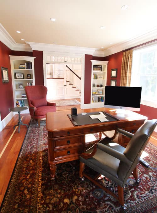 Traditional Home Office With Crown Molding, Red Walls, White Trims,  Built In Shelving And A Large Oriental Rug On Hardwood Flooring.