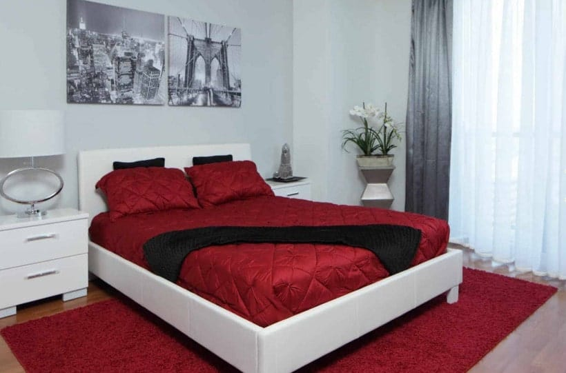 A focused shot at the master bedroom's modish white and red bed setup with two white bedside tables and attractive wall decors.