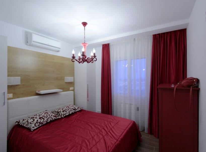 Small master bedroom featuring a red comfy bed along with a red cabinet and red window curtains. The room is lighted by a fancy chandelier.