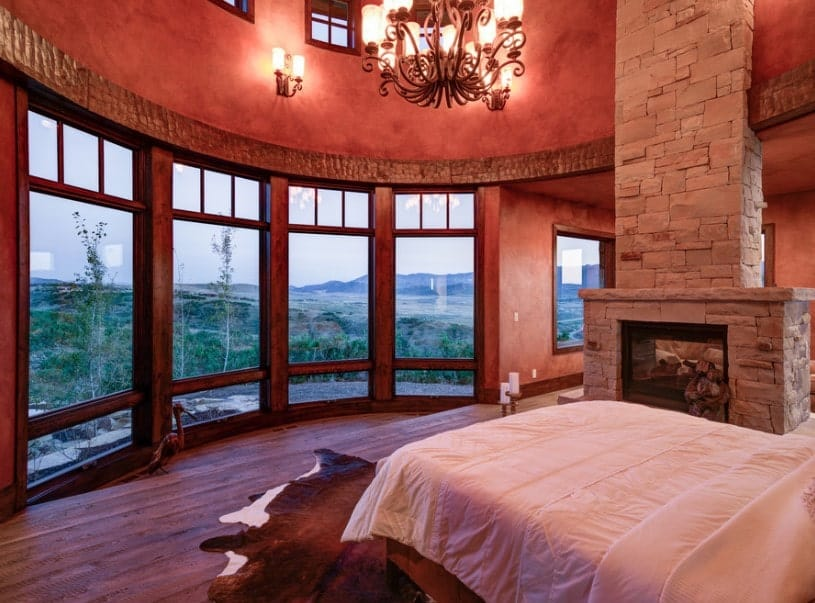 A master bedroom boasting a well-placed bed in front of the glass windows overlooking the stunning outdoor views. The room offers a fireplace and is lighted by a fancy chandelier.