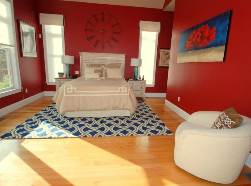 Master bedroom with a classy bed setup lighted by two table lamps and is surrounded by red walls.