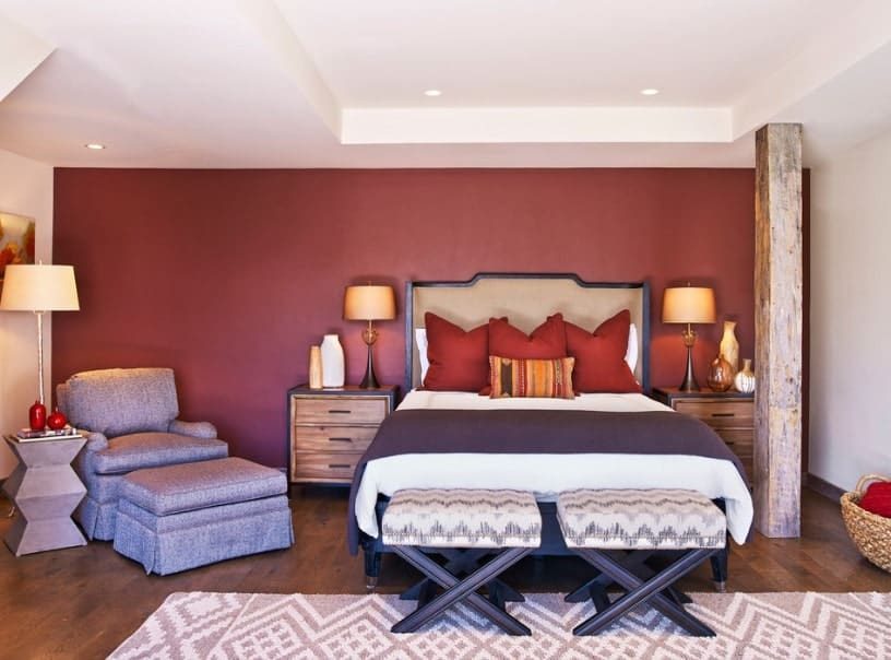This master bedroom features a white ceiling and hardwood flooring, along with red walls. The room has a cozy bed lighted by table lamps on top of bedside tables on both sides.