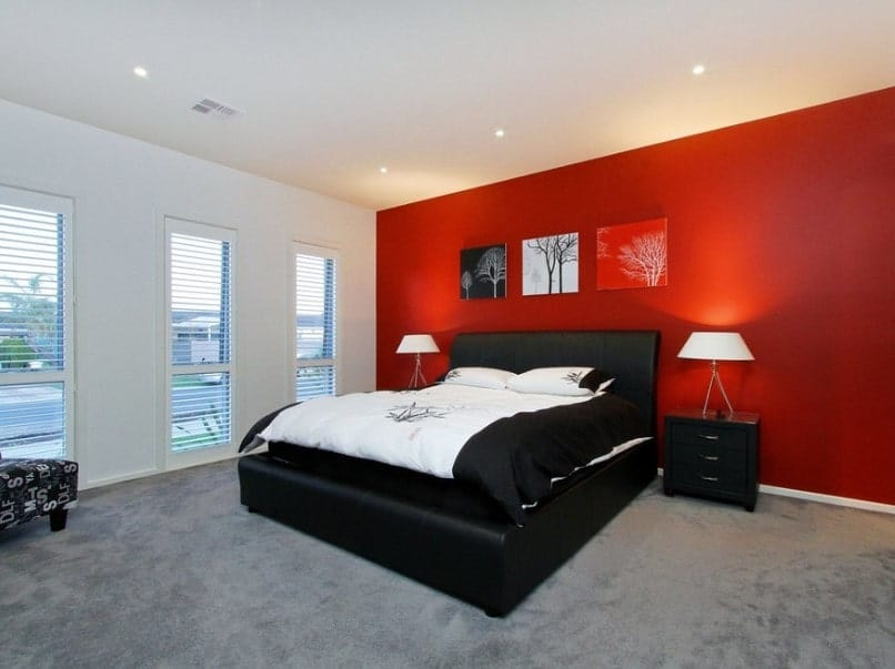 Modern master bedroom featuring a red and white wall color combination. It also has a white ceiling and gray carpet flooring, along with a black bed frame.