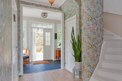 Scandinavian foyer with white front double doors and multi-colored interior wallpaper.