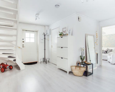 Scandinavian foyer with white front door, white walls and light wood flooring.