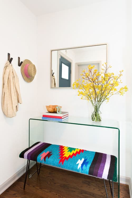 Tiny Scandinavian foyer with white walls, hooks, a colorful bench seating, dark wood floors and mirror and glass table for added visual space.