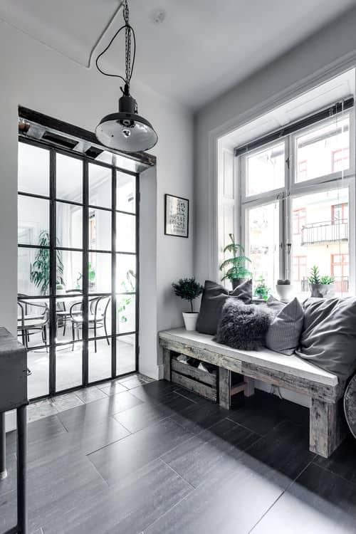 Small Scandinavian foyer with white walls, pendant lighting and black hardwood flooring.