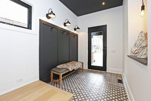 Scandinavian foyer with white walls, black front door, wall lights and ceramic tile flooring.