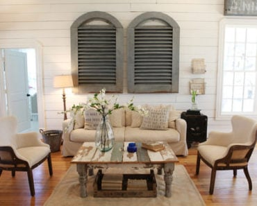 Barn-style Shabby-Chic formal living room with white shiplap wall panels, a distressed coffee table and medium-tone wood flooring.