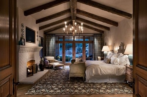 Southwestern master bedroom with beam ceiling, chandelier, brick fireplace and beige walls.