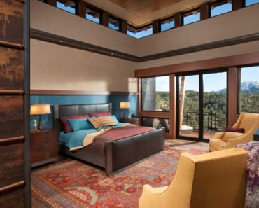 Large Southwestern master bedroom with 2-story ceiling, beige walls and carpet flooring.