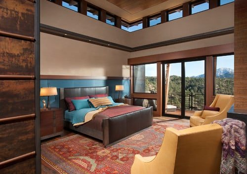Large Southwestern Master Bedroom With 2 Story Ceiling, Beige Walls And  Carpet Flooring.