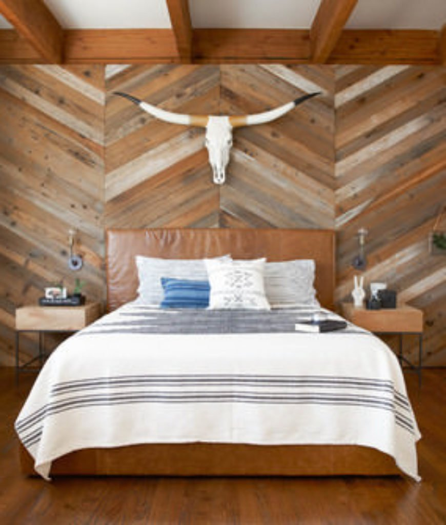 Southwestern master bedroom with beam ceiling, reclaimed wood wall pattern and interior wallpaper.