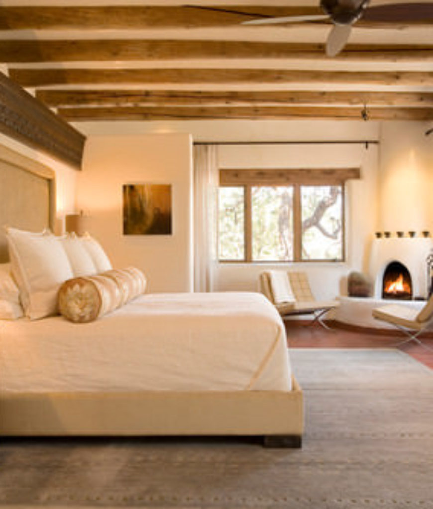 Southwestern master bedroom with beam ceiling, beige walls and corner fireplace.