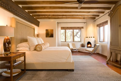 Southwestern Master Bedroom With Beam Ceiling, Beige Walls And Corner  Fireplace.Photo By Samuel Design Group   Discover Bedroom Design Ideas