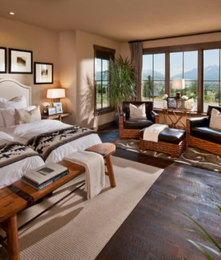 Southwestern guest bedroom with twin beds next to each other and a seating area by the window.