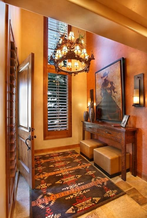 Small Southwestern foyer with chandelier, orange walls and a console table.