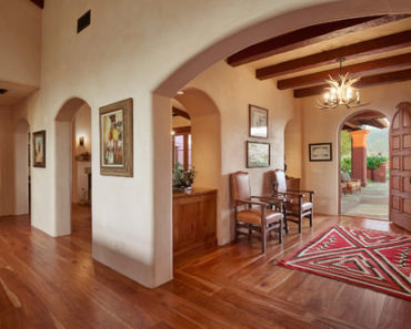 Mid-sized Southwestern foyer with beam ceiling, chandelier, wood arch front door and arch doorways.
