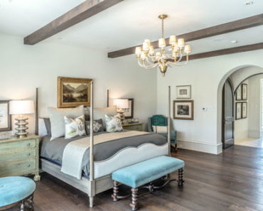 Southwestern master bedroom with beam ceiling, chandelier and white walls.