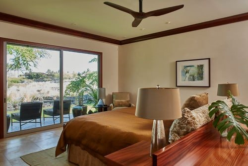 Tropical Master Bedroom With Built In Desk, Tile Flooring And Glass Sliding  Doors Offering