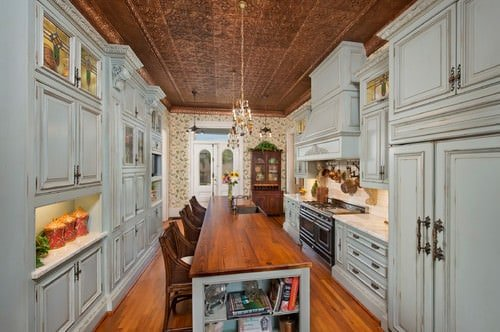 Luxury galley kitchen with decorative ceiling, a chandelier, distressed white cabinets, interior wallpaper, and a long base cabinet island with wood surface, sink, and chairs.