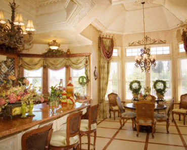 Large Victorian dine-in kitchen with tall ceiling and warm tone colors.