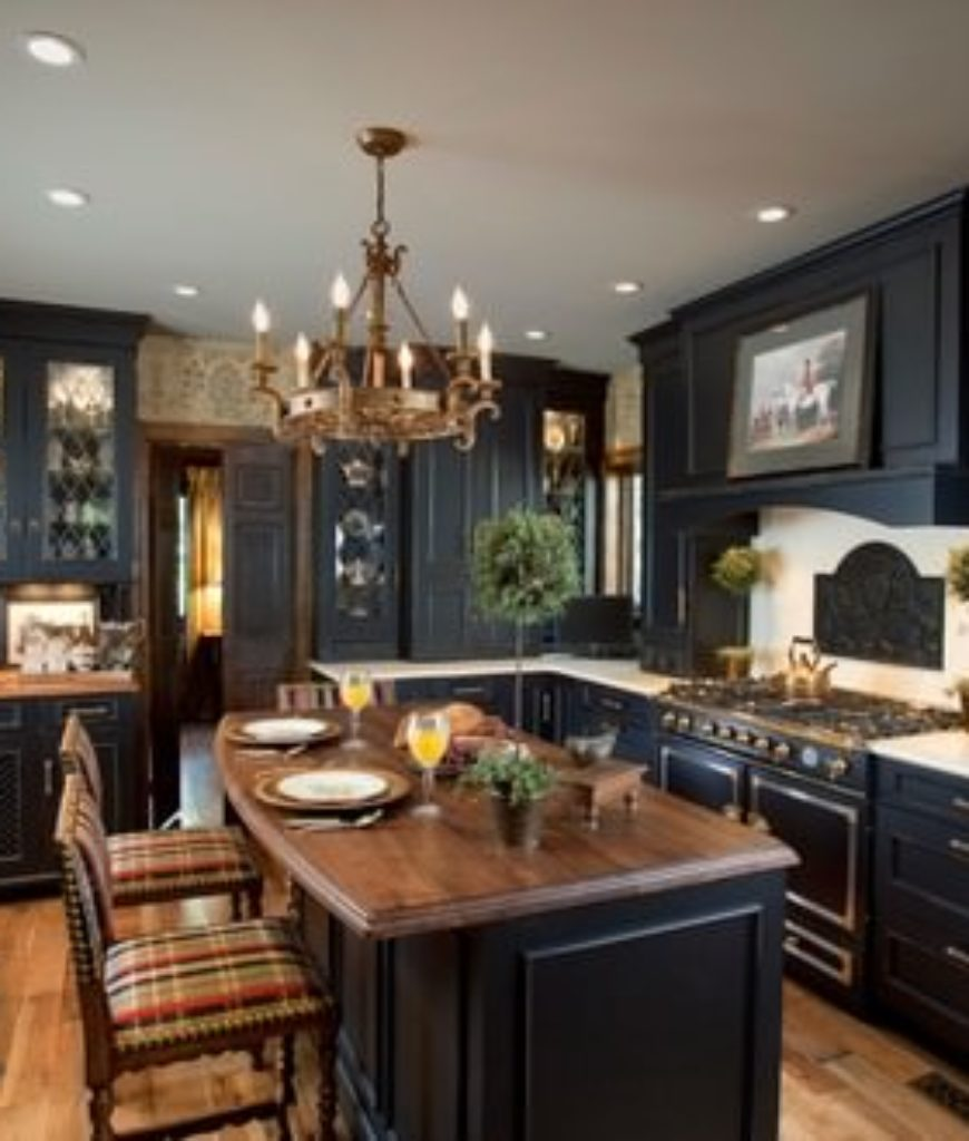 Victorian kitchen with black cabinets, black appliances and beige backsplash.