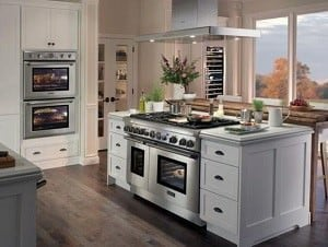 Kitchen island with an oven and a matching cooking range and hood.