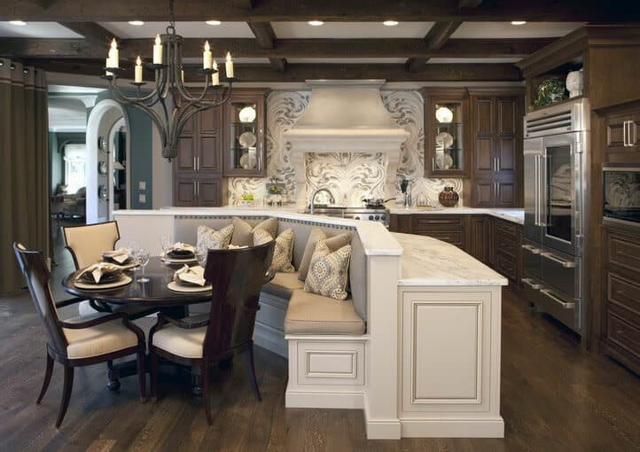 White kitchen island with breakfast nook stands out in this dark kitchen. It includes a round dining table surrounded with beige upholstered chairs and lighted by a vintage chandelier.