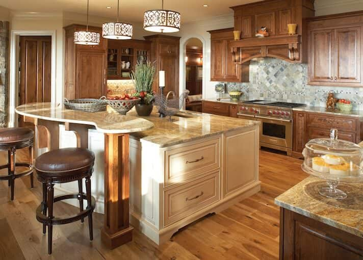 Spacious brown toned kitchen with an elaborate breakfast island bar, hardwood floors, wooden cabinetry, and decorative pendant lights.