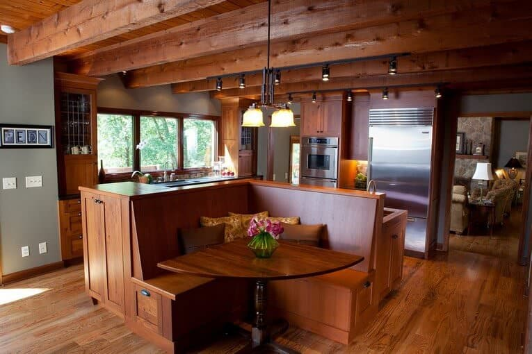 An all wood kitchen boasting a unified look. It has a kitchen island and breakfast nook combo lighted by warm pendant and track lights fixed to the wood beam ceiling.