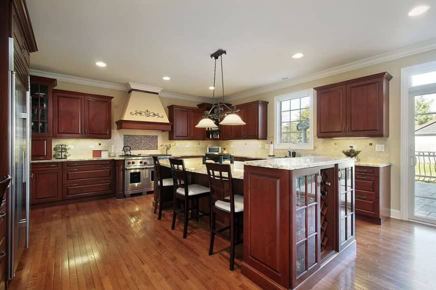 Spacious U-shaped kitchen with wooden cabinetry, marble countertop central breakfast island, and hardwood floors.