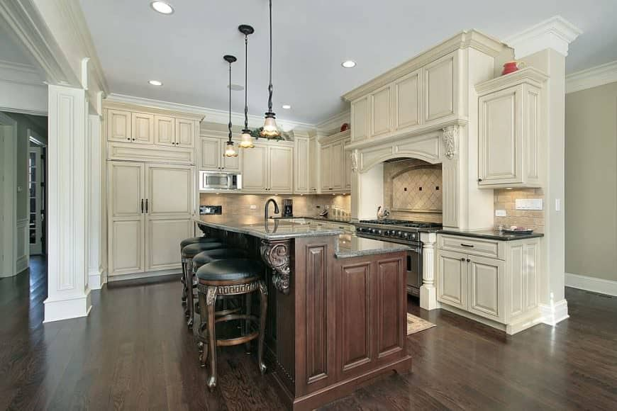 Cream themed L-shaped kitchen with farmhouse style cabinetry, vintage stool pieces, dark brown breakfast island, and dark hardwood floors.
