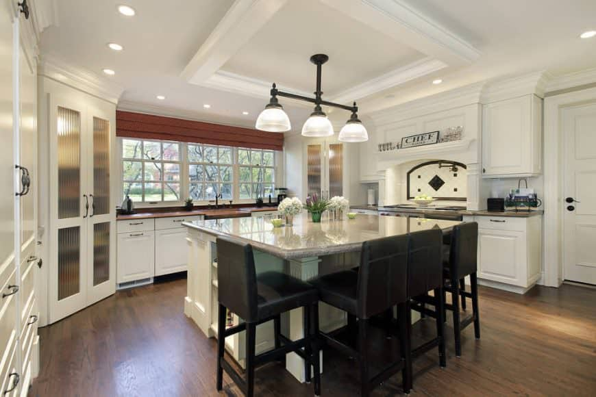 White kitchen with large square white island and dark stools. The notable feature of this island is the square shape (most islands are rectangular). The dark stools work well with the white kitchen design.
