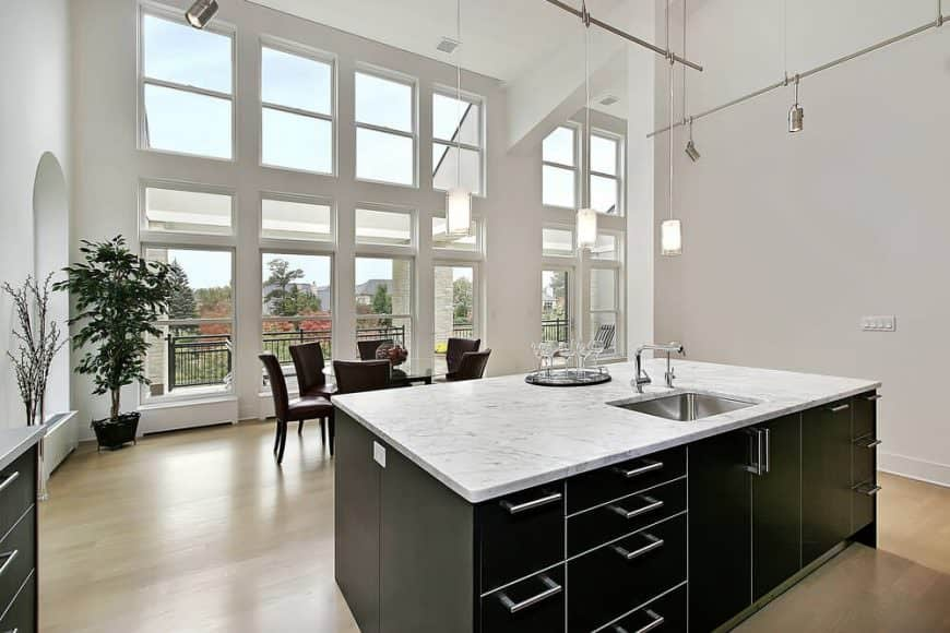 Modern midcentury kitchen with black island, hardwood floors, high ceiling, stylish pendant lights, and tall windows.