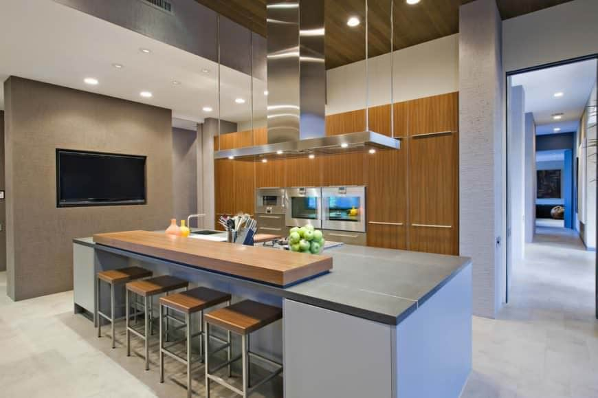 Modern kitchen set with a long center island featuring a cozy bar area for four persons. Recessed lights scattered on the ceiling to illuminate the whole kitchen space.