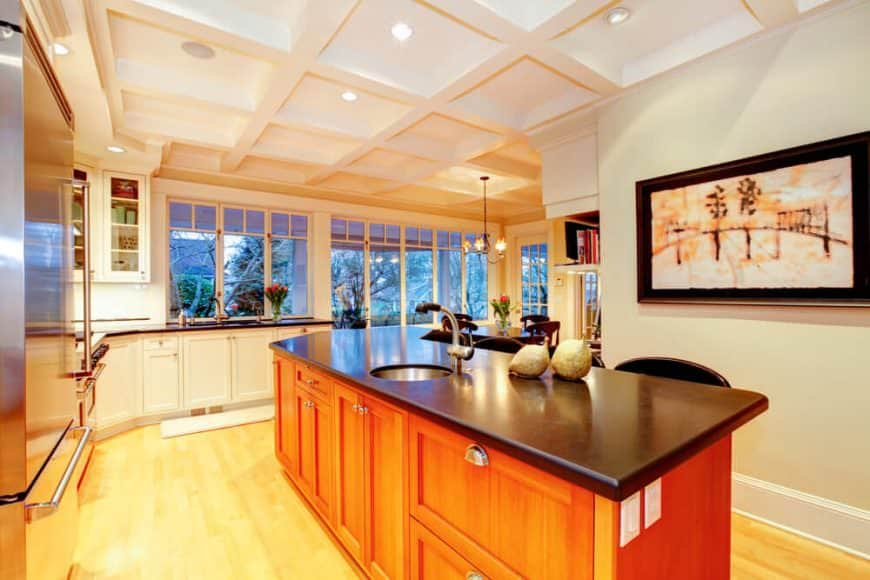 Elegant kitchen with white coffered ceiling, hardwood floors, angled breakfast island, and white cabinetry.
