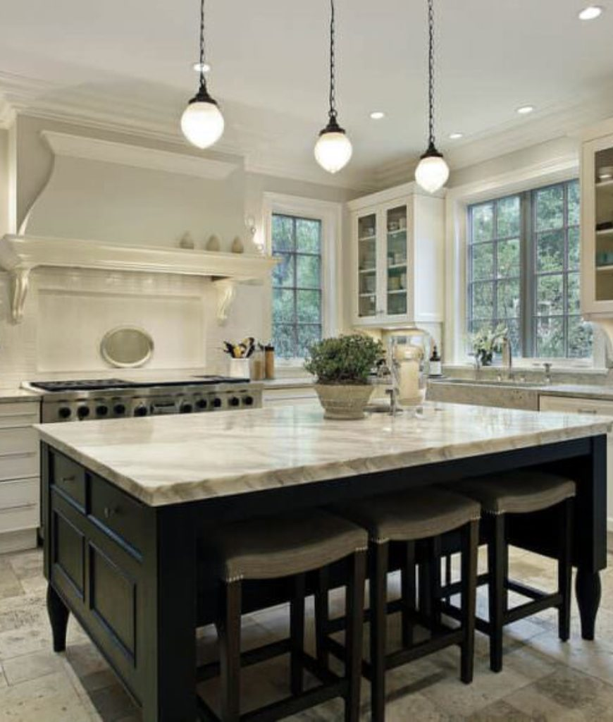 White kitchen with dark wood island. Notable feature of this island is how the stools tuck entirely under the island counter top.