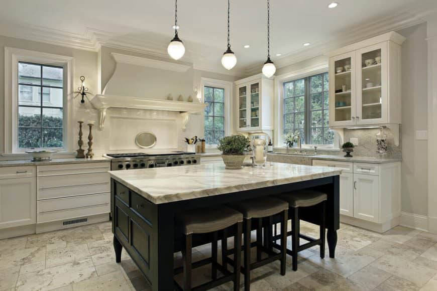 White kitchen with dark wood island. It has a marble countertop and space for a breakfast bar for three and is lighted by pendant lights.