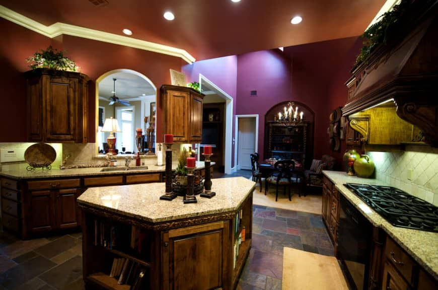 Angled kitchen island in the large kitchen area. This island is an example of a unique shape in order to fit within the kitchen layout. The room has purple walls and dim lighting from the chandelier and recessed lights.