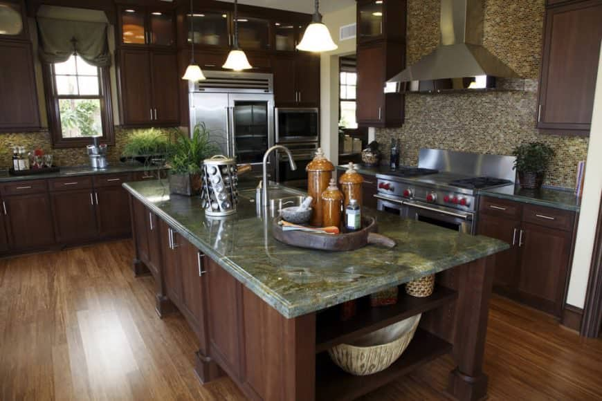 Dark wood island with green granite counter top matches kitchen cabinets.