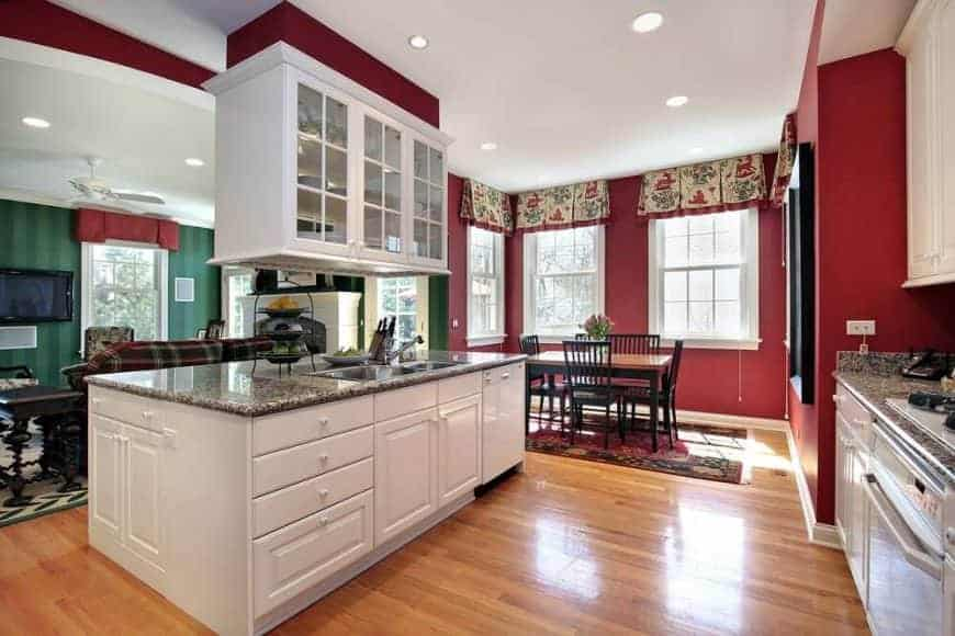 Red kitchen situated behind the green living room with hanging front glass cabinets suspended over the white kitchen island. It includes a wooden dining table paired with black chairs that sit on a vintage rug.