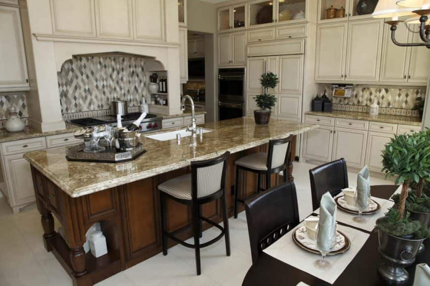 This dine-in kitchen features a dark wood breakfast island topped with a marble counter and surrounded with white cabinetry.