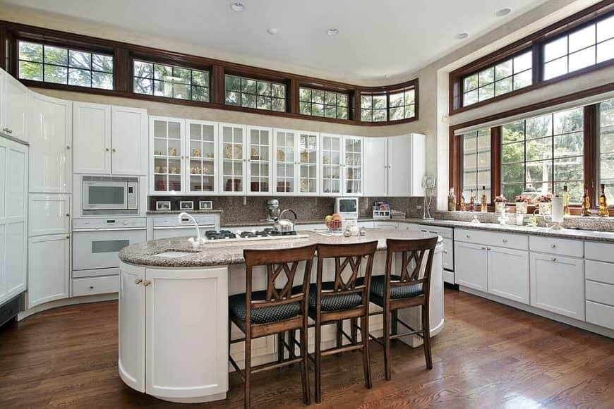 Elegant U-shaped kitchen with hardwood floors, oval-shaped breakfast island bar, polished white cabinetry, tall ceiling, and recessed lighting.