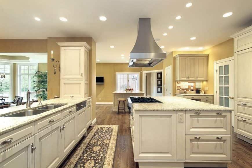 This large kitchen boasts a large center island and a peninsula both with marble countertops, lighted by recessed ceiling lights.