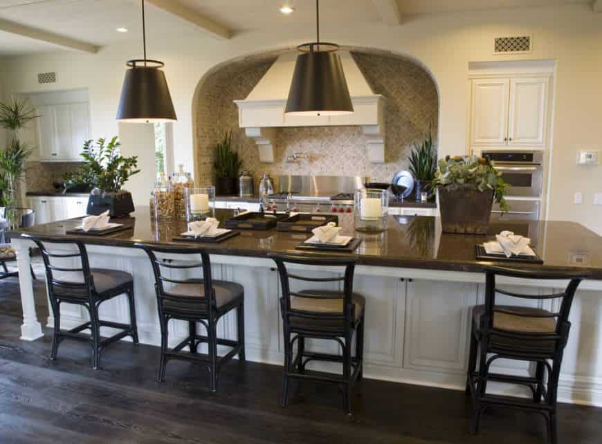 A pair of black pendants hang over a white breakfast island aligned with black chairs in this small kitchen. It has a stone brick stove alcove with white vent hood fixed to the diamond patterned tile backsplash.