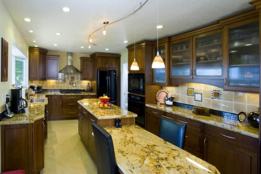 This kitchen offers marble countertops. The brown cabinetry looks perfect with the recessed and pendant lights brightening the space. There's a narrow center island as well providing space for a breakfast bar.
